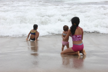 sisters playing in the waves